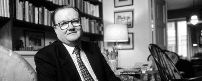 En man i kostym och glasögon sitter i en fåtölj i ett vardagsrum.