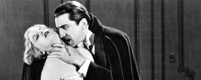 Svartvit bild från filmen Dracula år 1931: Vampyren Dracula lutar sig över sitt offer.