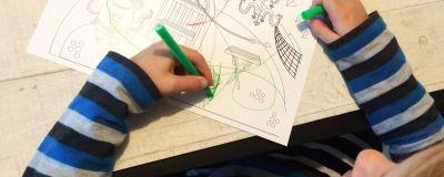 Lapsi värittää Pikku Kakkosen Eskarin värityskuvaa