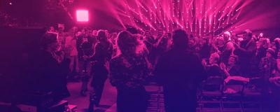 Människor som står upp och klappar i händerna i en konsertlokal med ett lila-rosa sken.