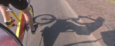 Pedalarna och skuggan av en cykeltaxi syns mot asfalten.