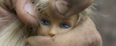 Smutsig hand klämmer Barbie-docka.