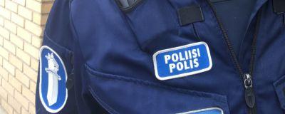 Polisdräkt i mörkblått och med olika polismärken på.