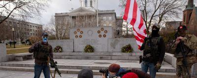Beväpnade män ur Boogaloo-rörelsen står framför New Hampshires delstatsregeringsbyggnad i staden Concord.