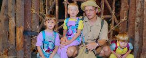 Kuvassa lapsia värikkäissä vaatteissa ja ohjelman juontaja safari-vaatteissa.