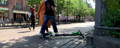 En elsparkcykel ligger på gatan, och tre personer går förbi den, en kliver över.