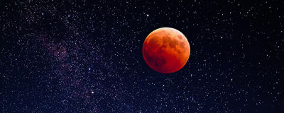 En röd måne och en stjärnhimmel.