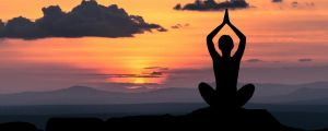 Person som mediterar i solnedgången.