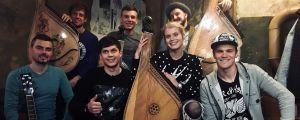 Alina Tomnikov istuu kuusijäsenisen yhtyeen keskellä.