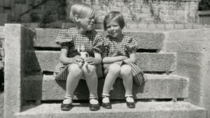 Meri ja pikkusisko Ritva istuvat rappusilla. Merillä on pieni nukke sylissään.