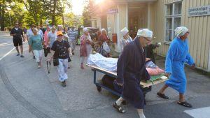 Ett tjugotal människor går i grupp med sjusovaren på en rullande säng längst fram.