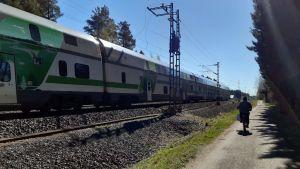 En tåg kör förbi en cyklist på en grusväg.