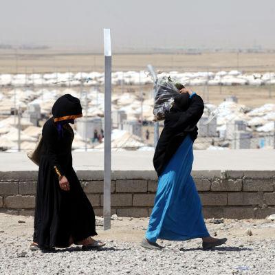 Två kvinnor går utanför ett flyktingläger i Irak.