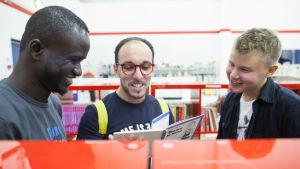 tre män läser tillsammans en bok