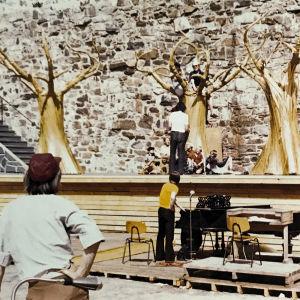Olavinlinnassa 1970-luvulla Taikahuilu-oopperan lavasteista kolme kultaista puuta. Kuva harjoituksista jossa muutamia esiintyjiä ja teknistä henkilökuntaa.