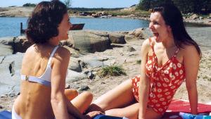 Kaksi naista istuu rannalla uimapuvuissaan, pyhkeen päällä ja nauraa.