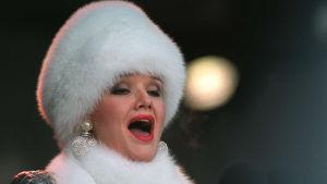 Oopperalaulaja Karita Mattila laulaa valkoisessa turkishatussa