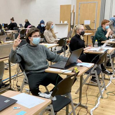 Ylioppilaskirjoitukset salissa, harmaaseen villapaitaan pukeutunut Ilkka Regelin viittaa.