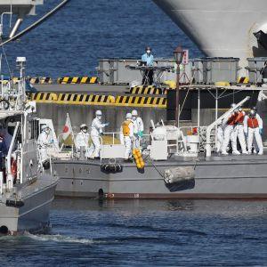 Räddningsarbetare i skyddsdräkter förde i land de smittade från Diamond Princess i Yokohama på onsdagen.