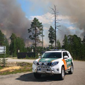 Gränsbevakningens bil med mycket rök i bakgrunden från skogsbränderna i Raja-Jooseppi i Lappland.