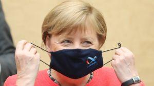 Merkel riisuu maskia, jossa on Saksan EU-puheenjohtajuuslogo.