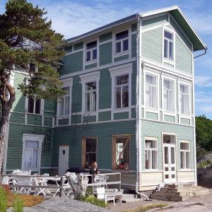 En grön villa på en klippa vid havet.