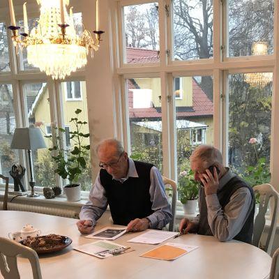 Karl-Olof Fagerström och Ingemar Wemmenhög från Waxholmspartiet sitter vid ett bord i en glasveranda med papper framför sig.