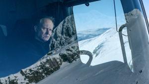 Karaktären Nils sitter i hytten på plogbilen och omgivningen spelad i vindrutan.