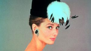 Audrey Hepburn poseeraa lähikuvassa. Kuva elokuvasta Aamiainen Tiffanylla.