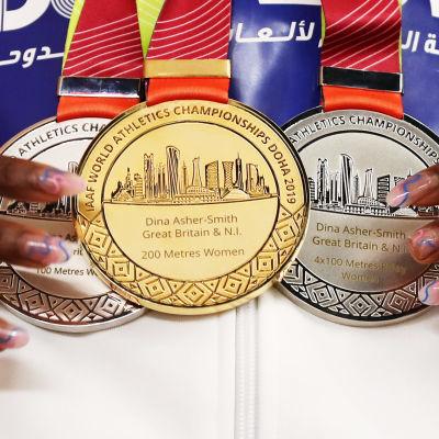 Två silvermedaljer och en guldmedalj hängandes kring Dina Asher-Smiths hals.