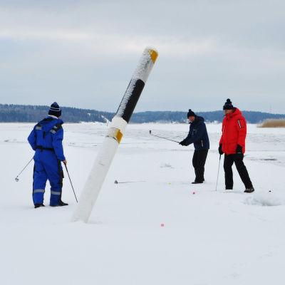 Fem herrar står på isen bredvid ett sjömärke och spelar golf.