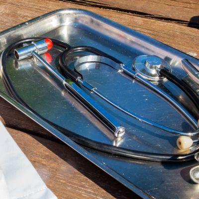 Lääkäri-instrumentteja metallitarjottimella ja lääkärin takki sivussa.