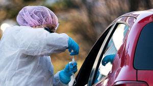 Mehiläisen drive-in-koronaviruksen testauspiste Espoon Tapiolassa 19.3.2020. Työntekijä ottaa testiä autossa istuvalta.