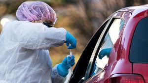 En anställd vid vårdbolaget Mehiläinen testar en patient för coronaviruset så att patienten sitter i sin bil.