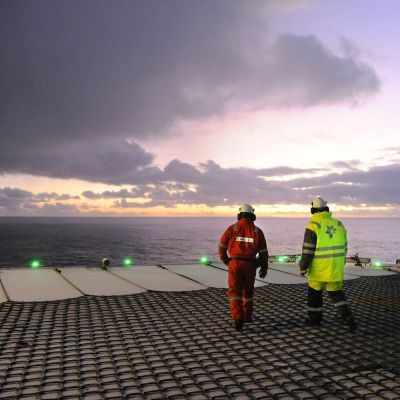 Två personer, den ena i röd overall och den andra i gul, går på däcket till en oljeplattform i solnedgången över Atlanten.