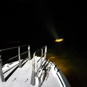 En båt vars däck syns och längre bort syns en sjunkande bastuflotte i havet.