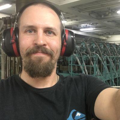En skäggig man med hörselskydd på som står i ett maskinrum i ett fartyg.
