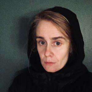 Elina Pirinen mustassa hupparissa, huppu päässä puolikuvassa