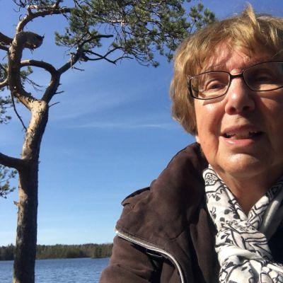 en äldre kvinna som sitter vid havet och tittar mot kameran.