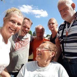 Medelålders och lite äldre personer med funktionsnedsättning samt två yngre vårdare ser glada ut i en gruppbild. Sol och sommar.