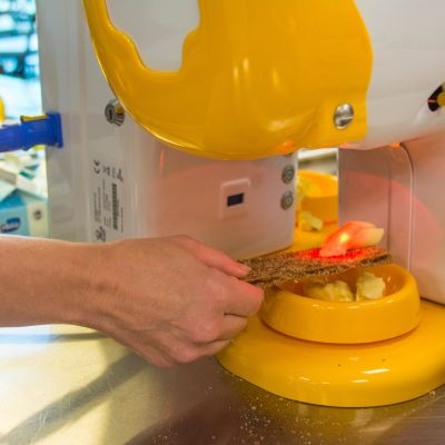 Voikone pudottaa annoksen levitettä näkkileivän päälle.