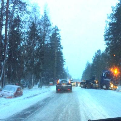 En isig landsväg där en bil står i diket och en långtradares dragbil står snett över vägen. Bilar kör försiktigt förbi.