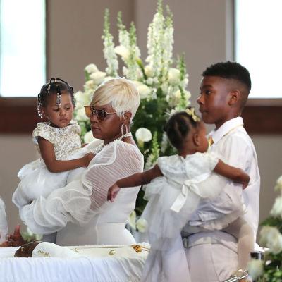 Vitklädd kvinna står med vitklädda barn vid kistan där Rayshard Brooks ligger. Kvinnan är hans änka.