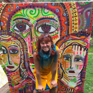 Kuvataiteilija Paula Huhtanen Nokian Sarkolassa, taustalla värikäs Naarasikoni-maalaus.
