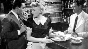 Mies ja nainen ovat baaritisklillä, nainen tarjoilijan asussa. Baaritiskin takana on mies valkoisessa puvussa.