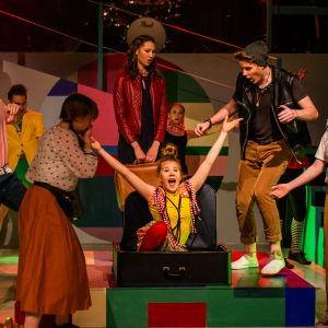 En flicka i gul skjorta kommer ut ur en kappsäck i en ungdomsshow i Pargas.