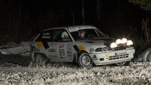 Rallybil kör i vinterterräng.
