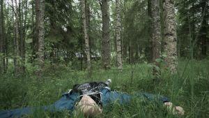 Mies makaa selällään ruohikossa metsän laidalla.