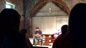 En man sitter med ett gevär i handen på en köksbänk på en teaterscen i en gammal industribyggnad.