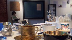 Fina gamla kaffekoppar på ett bord. I bakgrunden föremål från en skola på 1800-talet eller tidigt 1900-tal.
